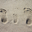 Three family footprints in sand - ストック写真