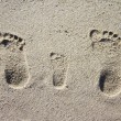 图库照片: Three family footprints in sand