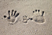Family palm imprints on sand — Stock Photo