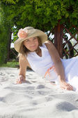 Woman with hat lying on white sand — Stock Photo