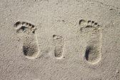 在沙子中的三个家庭脚印 — 图库照片