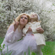 Happy mother and daughter among spring garden blossom — Foto Stock