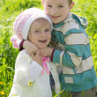 Brother giving hug to sister outdoors - Stock Photo