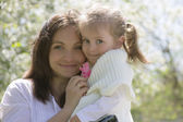 Happy mothre and baby girl in garden — Stock Photo