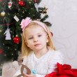 Girl in pink under Christmas tree — Stock Photo