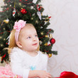 Amazed little girl under Christmas tree — Stock Photo