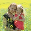 Foto Stock: Mother and daughter in rapeseed field