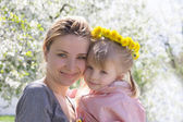 Happy mothre and baby girl in spring garden — Stock Photo