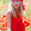 Woman in long red dress among poppy field — Foto Stock