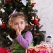 Little girl under Christmas tree with gifts — Stock Photo