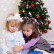 Two girls under Christmas tree — Stock Photo