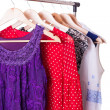 Dresses of different colors on wooden hangers — Stock Photo