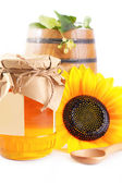 Jar and barrel with honey and flowers — Stock Photo