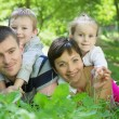 Family with two children lying down in the park — Stock Photo
