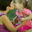 Stock Photo: Happy mother and little daughter kissing in meadow