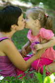 Happy mother and little daughter kissing in meadow — Stock Photo