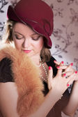 Retro woman in hat and boa with eyes closed — Stock Photo