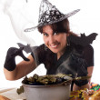 Stock Photo: Smiling witch making magic on Halloween