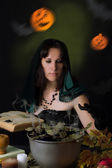 Witch making magic with book — Stock Photo