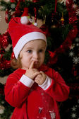 Little girl putting wishes under Christmas tree — Stock Photo