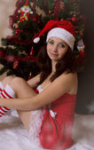 Santa woman helper sitting next to Christmas tree — Stockfoto