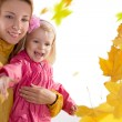 Mother and daughter catching falling leaves — Stock Photo