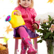 Girl in raincoat and boots with autumn leaves — Stock Photo #30648815