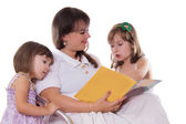 Two daughters listening their mother reading book — Stock Photo