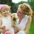 Mother and daughter among pink rose garden — Stock Photo