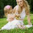 Mother and smiling daughter sitting on grass — Stock Photo #30868811