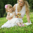 Mother and smiling daughter sitting on grass — Stock Photo