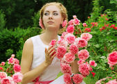 Woman in pink rose garden walking — Stock Photo