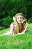 Woman with roses lying among green grass — Stock Photo