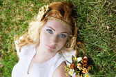 Red-headed woman lying on green grass — Foto Stock