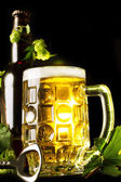 Mug of golden beer, bottle and openner with hop leaves — Stock Photo