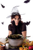 Pretty witch making magic on Halloween — Stock Photo