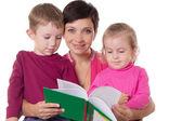сын и дочь, слушая их матери чтения книги — Стоковое фото
