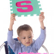 Boy with colorful letters in raised hands — Stockfoto