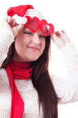 Smiling woman in Santa hat lifting heart-shaped glasses up — Stok fotoğraf