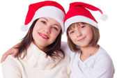 Smiling mother and daughter in Santa hats — Stock Photo