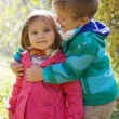 Brother hugging sister in autumn park — Stock Photo
