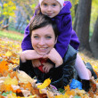 Mother and little daughter lying among autumn leaves — Stock Photo