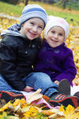Sister and brother together on autumn leaves — Stock Photo