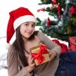 Teen girl in Santa hat with gifts under Christmas tree — Zdjęcie stockowe