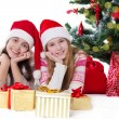 Smiling sisters in Santa hats lying under Christmas tree — Stock Photo