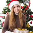 Teenage girl in Santa hat with present under Christmas tree — Stock Photo