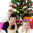 Stock Photo: Mother with two children under Christmas tree