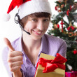 Service operator on Christmas back showing ok sign with present — Stock Photo
