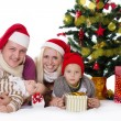 Happy family with two children in Santa hats under Christmas tree — Stock Photo