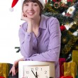 Woman with clock under Christmas tree — Lizenzfreies Foto